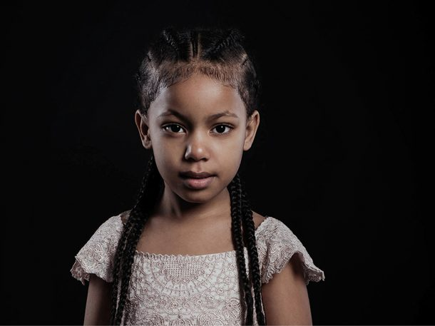 Portrait of young girl looking direct to camera side lit with cane rowed plaits